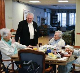Father Dan Hopcus, a Providence Associate and chaplain for the Sisters of Providence at Saint Mary-of-the-Woods, enjoys his daily visits to sisters and other residents at Providence Health Care. Here, Father Dan visits with Sister Anne Krause (formerly Sister Marie Robert) and Mary Imelda Coulup.