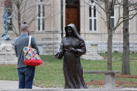 Providence Associate Kyle Meadors spends some reflective time near the statue of Saint Mother Theodore Guerin.