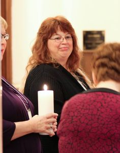 Donna Snelling carries a candle prepares to carry a candle in the procession at her first commitment liturgy as a Providence Associate in 2014.