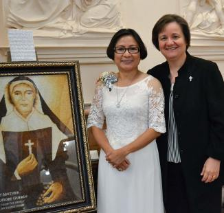 Sister My Huong Pham, celebrating 25 years as a sister, center, with Sister Anne Therese Falkenstein, right, pose with the rice artwork of Saint Mother Theodore Guerin at left, a gift from Sister My Huong's family on the occasion of her jubilee.
