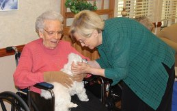 Judy Collins takes a moment to pet Benny who is content on the lap of Sister Mary Louise O'Connor.