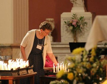 Sister Dawn Tomaszewski lights her candle as a chapter delegate during the opening ritual. At the end of the chapter she would be elected the next general superior. (photo by Amy Miranda)