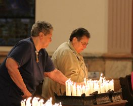 Chapter delegates (voting members) are called forward to light a candle during the opening ritual for Chapter. Here Sisters Jo Paolinelli and Andre Panepinto place their lit candles among those representing other sister delegates. (photo by Amy Miranda)
