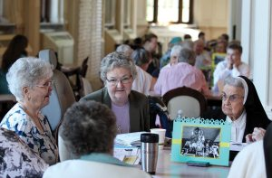 From left, Sisters Marikay Duffy, Therese Guerin Sullivan, and Helen Therese Conway participate in conversation at their table.