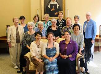 The whole group poses with Emily after the knocking ritual. Front row from left, Sister Anna Fan, Emily TeKolste, Sister Joni Luna. Second row from left, Sisters Nancy Nolan, Marsha Speth, Nancy Bartasavich, Denise Wilkinson, Mary Beth Klingel, Editha Ben. Back row from left, Sister Carole Kimes, Janice Smith, Jenny Howard, Dawn Tomaszewski, Jeanne Hagelskamp and Lisa Stallings.