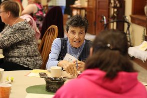 Sister Paula Modaff speaks with those at her table.