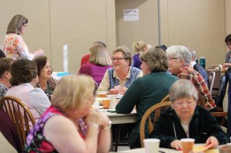 Sisters of Providence companion Sister Terri Boland, center, chats with those at her table during the orientation.