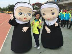 "Sister Norene Wu with characters ""Peace and Joy,"" mascots for the 60th anniversary."