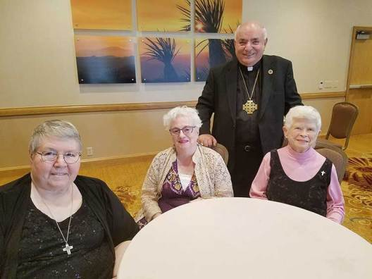 San Bernardino Bishop Gerald Barnes (standing) with Sisters of Providence (from left) Cathy White, Loretta Picucci and Carol Nolan.