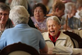 Sister Mary Rita Griffin reacts with delight to something said by a person at her table.