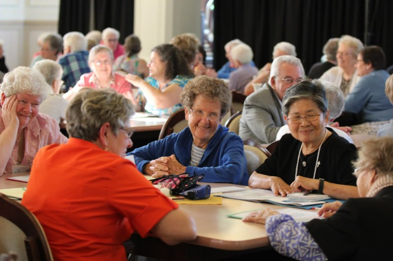 Smiling during table discussion are, from left, Sisters Jan Crave, Josephine Bryan and Celeste Tsai.