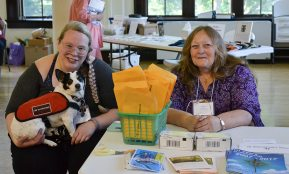 Say cheese, Gary! Posing at the sign-in table are Providence Associates Kaitlyn Willy (with her service dog Gary) and Anne Shupe-Scurry.