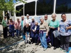 Sisters, volunteers and staff pose outside the bus during an excursion.
