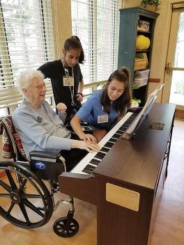 Sister Margaret Nau (sitting) receives help playing the piano from Jolyssa Cortez and Iliana Bocard.