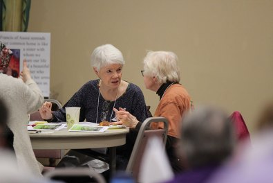 Providence Associate candidate Mary Heins speaks with another attendee at her table.