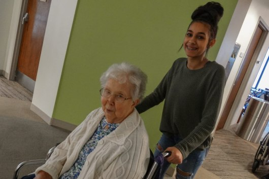 A volunteer helps a Providence Health Care resident get to the performance