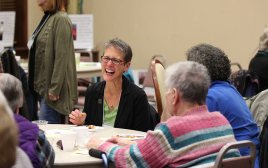 Providence Associate Maria Price laughs while talking with those at her table.