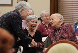 Joyful welcome! Sister Rosemary Nudd shakes hands with Providence Associate Father Bernie Lutz as Providence Associate Deanna Ruston smiles.