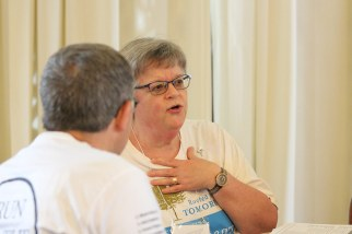 Sister Beth Wright speaks with an associate at her table during Monday's meeting.