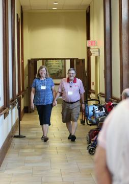 Providence Associate couple Eileen and Joe Horan hold hands while walking down the hall to the Saturday social.