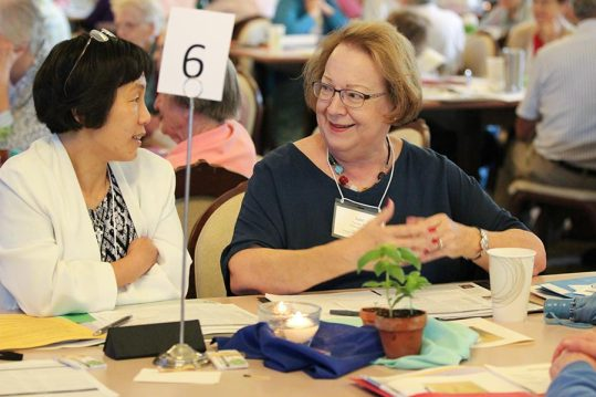 Sister Anji Fan and Providence Associate Jane Fischer speak at their table during Monday's SP meeting with associates.