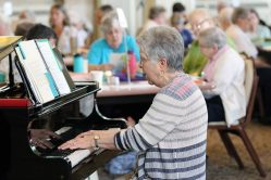 Providence Associate and liturgy staff member Karen Sagraves plays the piano during a prayer time at Monday's meeting with sisters and associates.