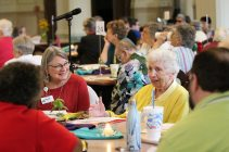 Sister Marilyn Ann Kofler, right, speaks with those at her table, including Lorrie Heber, left, director of White Violet Center for Eco-Justice and member of the Justice Coordinating Commission of the Sisters of Providence.