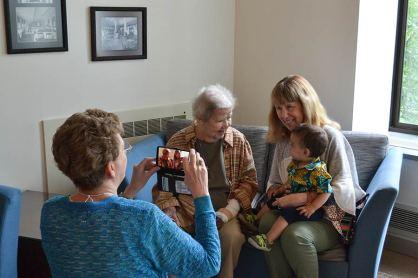 Sister Dawn Tomaszewski takes a photo of Sister Nancy Nolan with her Providence Associate companion Mel Marino Wolff and her baby grandson.