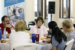 Providence Associate Anne Mosher speaks with others at her table on Saturday.