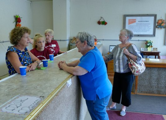 Jeanette Wrin (left) joins other volunteers who are prepared to answer visitor questions about how the pantry works.