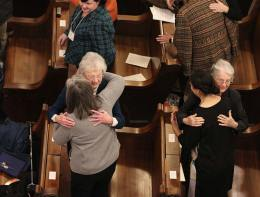 Sister Marlyn Herber and Barbara Bluntzer hug their Providence Associate companions during the sign of peace