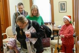 Sister Patty Wallace dressed as an elf sings and reads with children