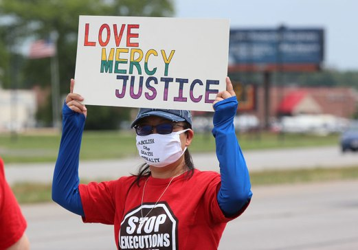 Sister Teresa Kang holds a love, mercy, justice sign during the anti-death penalty protest at US 41 and Springhill in Terre Haute on Wednesday.