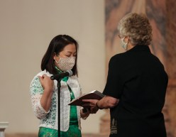 Sister Teresa Kang professes first vows. Sister Jenny Howard holds the Bible