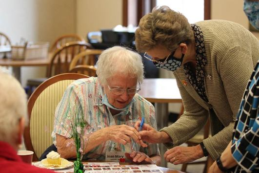 Sister Joan Mary Schaefer signs Sister Dawn Tomaszewski's placemat
