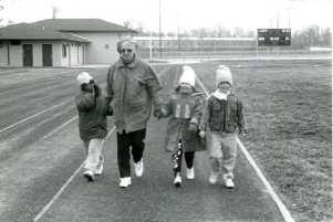 Sister Margaret Norris walking with children on the track at 10th Street School in Jasper, Indiana, during the 150th anniversary of the Sisters of Providence ministering in the city, which took place in 1992.