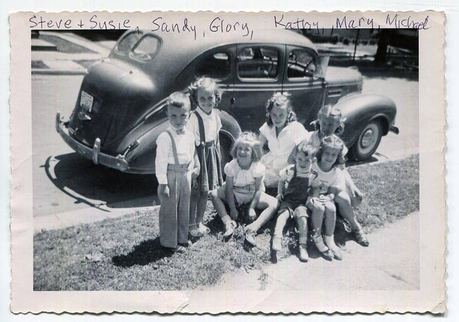 Children sitting in front of an old fashioned car.