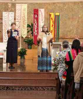 General Superior Sister Dawn Tomaszewski, left, and all gathered pray a blessing on Sister Joni.