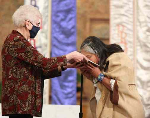 After professing her vows, Sister Joni kisses the Bible, held by General Officer Sister Lisa Stallings.