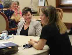 Kathleen Ly visits with those at her table before the morning reflection.