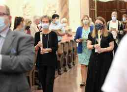 Mary Lou Kiesle and Erin Gick carry candles in the entrance procession as Tanya Pongracz follows with the book of readings.