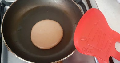 A very tiny pancake in a small pan next to a massive red spatula