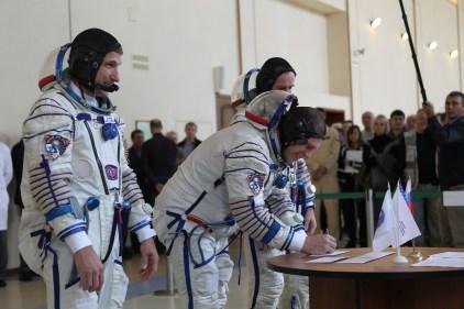 En el Centro de Entrenamiento de Cosmonautas Gagarin en la Ciudad de Las Estrellas, Rusia, la Expedición 37/38 Soyuz y su Comandante Oleg Kotov firman en una ronda de exámenes de calificación el 04 de septiembre, mientras sus compañeros de tripulación, el Ingeniero de Vuelo de la NASA Michael Hopkins (izquierda) y el Ingeniero de Vuelo de ROSCOMSOS, Sergey Ryazanskiy (parcialmente oculto detrás Kotov) observan. El trío está en entrenamiento final para su lanzamiento el 26 de septiembre, hora de Kazakstán, desde el cosmódromo de Baikonur en Kazakstán de la nave espacial Soyuz TMA-10M para una misión de 5 ½ meses en la Estación Espacial Internacional. NASA / Stephanie Stoll