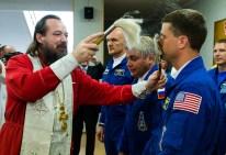 El ingeniero de vuelo Reid Wiseman de la NASA, a la derecha, recibe la tradicional bendición de ortodoxo padre Job, en el Hotel del Cosmonauta antes de su lanzamiento en el cohete Soyuz a la Estación Espacial Internacional, Miércoles, 28 de mayo 2014, en Baikonur, Kazajistán. Crédito de la imagen: (NASA / Joel Kowsky).