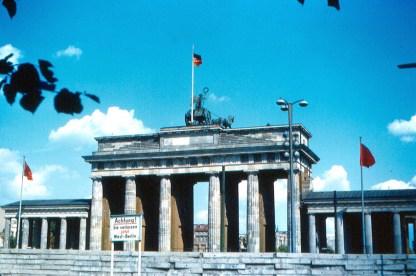En la imagen se puede ver la Puerta de Brandeburgo con la bandera de la RDA en en la parte superior del monumento. Las otras dos banderas son las de la Unión Soviética. Berlín, RFA, 15 de agosto de 1963. Foto: Roger Wollstadt/Flickr.