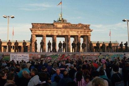 Los guardias de fronteras de la República Democrática Alemana de pie en el Muro de Berlín observan a las personas manifestarse el 09 de noviembre de 1989, Berlín, Alemania. Foto: Thomas Imo / Photothek través de Getty Images