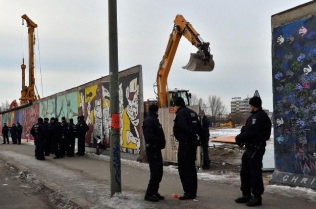 Agentes de policía custodian las obras de demolición en los sectores de la East Side Gallery, mientras son eliminadas partes del antiguo Muro de Berlín en Alemania, 27 de marzo de 2013. La intención de los inversores es la de construir un enorme edificio de apartamentos lujosos a orillas del río Spree. Foto: © Britta Pedersen/dpa/Corbis
