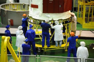 24 de agosto de 2015: Luego de que los diseñadores han completado su inspección, la nave Soyuz TMA-18M (módulo orbital) es integrada en el segmento PkhO que la conecta con el cohete portador Soyuz-FG. Foto: S.P. Korolev/RSC Energia.