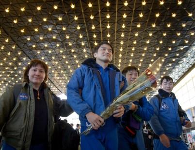 El astronauta de la JAXA Takuya Onishi es recibido con flores en el aeropuerto de Karagandá. Crédito de la imagen: NASA / Bill Ingalls.