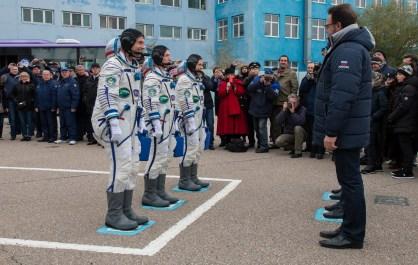 19 de Octubre de 2016: Los miembros de la Expedición 49 salen del edificio 254 y aguardan al saludo final ante las autoridades de la Comisión Estatal, antes de abordar la nave espacial Soyuz MS-02. Crédito de la imagen: NASA / Victor Zelentsov.